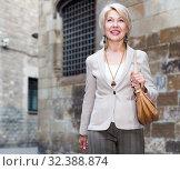 Купить «Adult woman 50s years old is walking in classic dress», фото № 32388874, снято 3 сентября 2017 г. (c) Яков Филимонов / Фотобанк Лори