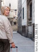 Купить «Mature woman tourist is walking in classic dress», фото № 32388878, снято 3 сентября 2017 г. (c) Яков Филимонов / Фотобанк Лори