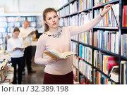 Купить «Young female looking for necessary books on shelves in bookstore», фото № 32389198, снято 22 февраля 2018 г. (c) Яков Филимонов / Фотобанк Лори