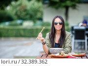 Young woman eating take away noodles on the street. Стоковое фото, фотограф Дмитрий Травников / Фотобанк Лори