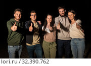 Купить «happy smiling friends showing thumbs up at night», фото № 32390762, снято 31 августа 2019 г. (c) Syda Productions / Фотобанк Лори