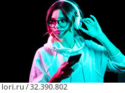 Купить «woman in headphones with smartphone in neon lights», фото № 32390802, снято 30 сентября 2019 г. (c) Syda Productions / Фотобанк Лори