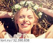 Купить «happy woman in wreath of flowers lying on straw», фото № 32390838, снято 31 июля 2016 г. (c) Syda Productions / Фотобанк Лори