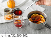 Купить «hand with ladle pouring hot mulled wine to glass», фото № 32390862, снято 4 октября 2018 г. (c) Syda Productions / Фотобанк Лори