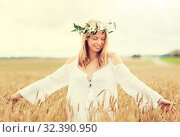Купить «happy young woman in flower wreath on cereal field», фото № 32390950, снято 31 июля 2016 г. (c) Syda Productions / Фотобанк Лори