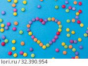 Купить «candy drops in shape of heart on blue background», фото № 32390954, снято 11 декабря 2018 г. (c) Syda Productions / Фотобанк Лори