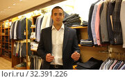 Smiling successful male administrator of clothing store standing behind counter on background of shelves with colorful garments. Стоковое видео, видеограф Яков Филимонов / Фотобанк Лори