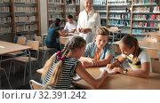 Купить «Teenage group of pupils sitting at table and studying, teacher in classroom», видеоролик № 32391242, снято 24 сентября 2019 г. (c) Яков Филимонов / Фотобанк Лори