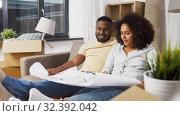 Купить «couple with boxes and blueprint moving to new home», видеоролик № 32392042, снято 3 ноября 2019 г. (c) Syda Productions / Фотобанк Лори