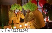 Купить «A man clown put on a green wig and smiling to the mirror», видеоролик № 32392070, снято 10 декабря 2019 г. (c) Константин Шишкин / Фотобанк Лори