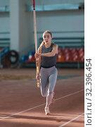 Купить «Pole vaulting - woman in gray leggings is running with a pole in her hands», фото № 32396454, снято 1 ноября 2019 г. (c) Константин Шишкин / Фотобанк Лори