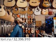 Купить «Young guy choosing acoustic guitar in music store», фото № 32396910, снято 11 сентября 2019 г. (c) Tryapitsyn Sergiy / Фотобанк Лори