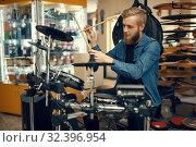 Купить «Young musician plays on drum set in music store», фото № 32396954, снято 11 сентября 2019 г. (c) Tryapitsyn Sergiy / Фотобанк Лори