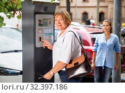 Купить «Smiling middle aged woman using parking machine to pay for car parking on summer city street», фото № 32397186, снято 16 февраля 2020 г. (c) Яков Филимонов / Фотобанк Лори