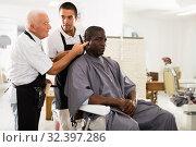 Купить «Aged barber teaching apprentice to male haircut», фото № 32397286, снято 22 августа 2019 г. (c) Яков Филимонов / Фотобанк Лори