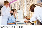 Купить «Two optometrists testing eyesight of woman», фото № 32397410, снято 27 августа 2019 г. (c) Яков Филимонов / Фотобанк Лори