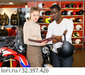 Купить «Polite smiling female seller communicating with male customer in modern motorcycle salon», фото № 32397426, снято 16 января 2019 г. (c) Яков Филимонов / Фотобанк Лори
