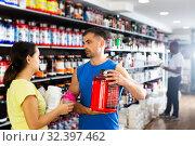 Купить «woman choosing diet and sports supplements and consulting seller», фото № 32397462, снято 9 декабря 2019 г. (c) Яков Филимонов / Фотобанк Лори