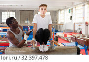 Купить «Male coach training teenage boy on gymnastic equipment at acrobatic hall», фото № 32397478, снято 17 января 2019 г. (c) Яков Филимонов / Фотобанк Лори