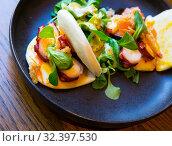 Купить «Seafood lunch. Tasty octopus tentacles with mango and bacon», фото № 32397530, снято 11 ноября 2019 г. (c) Яков Филимонов / Фотобанк Лори