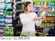 Купить «female customer looking at notes in shopping list», фото № 32398870, снято 23 ноября 2016 г. (c) Яков Филимонов / Фотобанк Лори