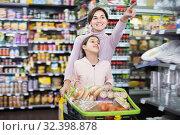 Купить «Positive woman and girl with shopping cart», фото № 32398878, снято 5 января 2017 г. (c) Яков Филимонов / Фотобанк Лори