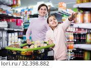 Купить «Adult woman and daughter with shopping cart», фото № 32398882, снято 5 января 2017 г. (c) Яков Филимонов / Фотобанк Лори