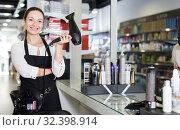 Купить «Positive young female hairstylist in apron with blow dryer», фото № 32398914, снято 31 марта 2018 г. (c) Яков Филимонов / Фотобанк Лори