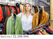 Купить «Positive girl looking for new leather jacket during shopping in retail shop», фото № 32398994, снято 5 сентября 2018 г. (c) Яков Филимонов / Фотобанк Лори