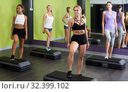 Купить «Portrait of fit woman performing step aerobics in fitness club», фото № 32399102, снято 26 июля 2017 г. (c) Яков Филимонов / Фотобанк Лори