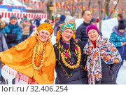 Russia, Samara, March 2019: Maslenitsa. People's celebration on the wires of winter. Two funny girls in Russian kokoshniks and bundles of pretzels on the neck. Редакционное фото, фотограф Акиньшин Владимир / Фотобанк Лори