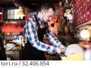 Купить «Male worker polishing buckle for belt», фото № 32406854, снято 13 ноября 2019 г. (c) Яков Филимонов / Фотобанк Лори