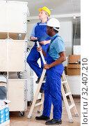 Купить «Two male builders working at indoors building site», фото № 32407210, снято 4 мая 2018 г. (c) Яков Филимонов / Фотобанк Лори