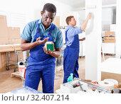 Купить «Two male builders working at indoors building site», фото № 32407214, снято 4 мая 2018 г. (c) Яков Филимонов / Фотобанк Лори