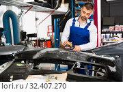Купить «Repairman sanding automobile bumper», фото № 32407270, снято 4 апреля 2018 г. (c) Яков Филимонов / Фотобанк Лори