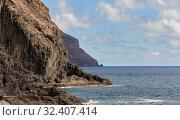 Купить «Picturesque landscape taken in Tenerife, Canary Islands, Spain. Rocky coastline black volcanic mountains cloudy sky and view to the calm Atlantic Ocean», фото № 32407414, снято 14 октября 2019 г. (c) Alexander Tihonovs / Фотобанк Лори