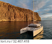 Moored lonely modern catamaran in calm waters of Atlantic Ocean near rocky volcanic cliff. Tenerife, Canary Islands, Spain. Concept of lifestyle, adventure activity, beautiful nature and freedom. Стоковое фото, фотограф Alexander Tihonovs / Фотобанк Лори