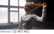 Купить «A young woman fencer she lets her hair down and shakes her head», видеоролик № 32407462, снято 21 февраля 2020 г. (c) Константин Шишкин / Фотобанк Лори