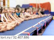 Купить «Gymnast girls sitting in line on gymnastic platform, unrecognizable children barefoot legs», фото № 32407886, снято 25 декабря 2013 г. (c) Кекяляйнен Андрей / Фотобанк Лори