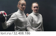 Купить «Two young women fencers in white protective suits standing in the dark studio - posing for the camera», видеоролик № 32408186, снято 21 февраля 2020 г. (c) Константин Шишкин / Фотобанк Лори