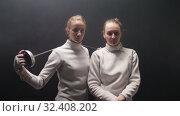 Купить «Two young women fencers standing in the dark studio - posing for the camera», видеоролик № 32408202, снято 1 апреля 2020 г. (c) Константин Шишкин / Фотобанк Лори