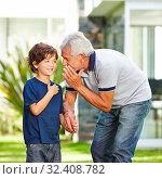 Opa flüstert seinem Enkel seinen Wunsch ins Ohr im Garten. Стоковое фото, фотограф Zoonar.com/Robert Kneschke / age Fotostock / Фотобанк Лори