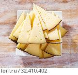 Купить «Slice of semi-hard cheese on a wooden table», фото № 32410402, снято 18 ноября 2019 г. (c) Яков Филимонов / Фотобанк Лори