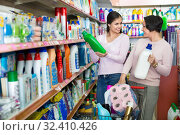 Купить «Young girl and mature woman choosing washing detergent», фото № 32410426, снято 14 ноября 2019 г. (c) Яков Филимонов / Фотобанк Лори