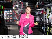 Купить «Sporty female is demonstraiting new rocket and ball for tennis in the store.», фото № 32410542, снято 7 февраля 2018 г. (c) Яков Филимонов / Фотобанк Лори