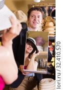 Купить «man holding mirror and showing customer his reflection in hats shop», фото № 32410570, снято 2 мая 2017 г. (c) Яков Филимонов / Фотобанк Лори