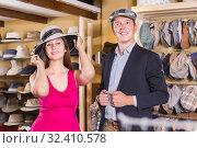 Купить «young wife and husband choosing dress hats in the store», фото № 32410578, снято 2 мая 2017 г. (c) Яков Филимонов / Фотобанк Лори