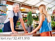 Frau redet mit Verkäufer an der Theke im Gartencenter. Стоковое фото, фотограф Zoonar.com/Robert Kneschke / age Fotostock / Фотобанк Лори