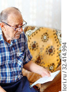An elderly man received a receipt for utility bills and asked how to live on a pension? Стоковое фото, фотограф Акиньшин Владимир / Фотобанк Лори