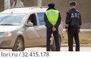 Купить «Russia, Samara, April 2016: two road patrol officers are standing on the road beside the car. Spring sunny day. Text in Russian: DPS.», фото № 32415178, снято 12 апреля 2016 г. (c) Акиньшин Владимир / Фотобанк Лори
